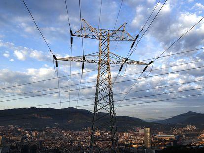 Una torre de transporte de energía, con la ciudad de Bilbao al fondo.