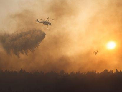 Un helicóptero vierte agua sobre el incendio en la zona de Varimpompi, al norte de Atenas.