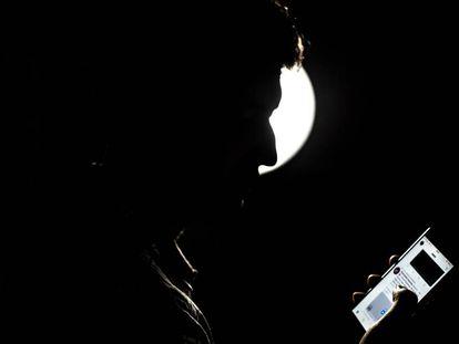 Un joven utiliza twitter desde su celular.