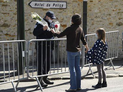 Una mujer entrega un ramo de flores a una policía junto a la comisaría de Rambouillet (cerca de París) donde fue asesinada una agente el pasado viernes.