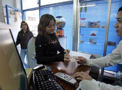 Inmigrantes ecuatorianas, en un centro de envío de dinero a su país, en Madrid.