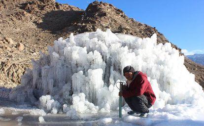 Un trabajador posa junto a una estupa de hielo en proceso de construcción.