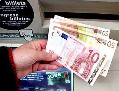 Un ciudadano de Banyoles (Girona) toca los nuevos billetes.