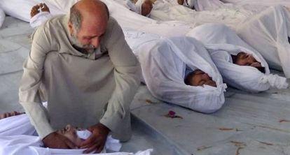 Un hombre llora sobre el cadáver de una víctima del supuesto ataque.
