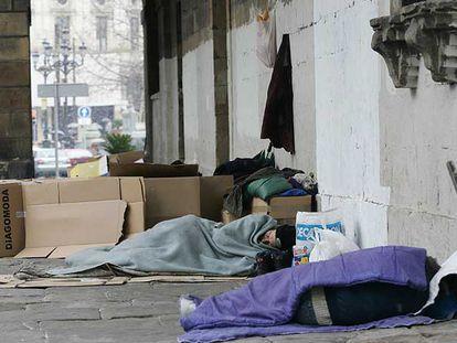 Varias personas sin hogar protegiéndose del frío con cartones y mantas  en pleno centro de Bilbao.