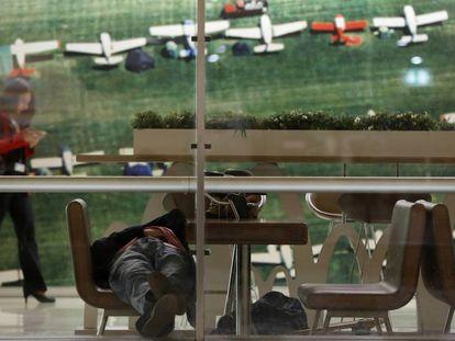 Uno de los viajeros fantasma que dice llamarse David descansa sobre una silla en el aeropuerto.