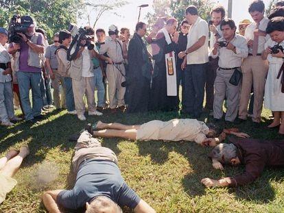 El arzobispo de El Salvador, rodeado de periodistas, junto a los cadáveres de las víctimas, en 1989.