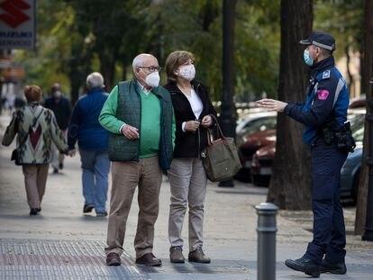 Un agente de la Policía Local de Madrid informa a una pareja sobre las medidas contra el coronavirus.