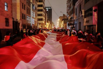 Una bandera de Perú sostenida por seguidores del candidato Pedro Castillo en el centro de Lima, este lunes.