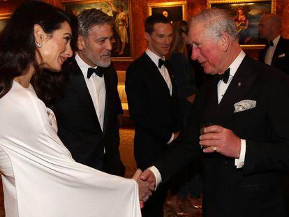 Amal y George Clooney jutno al príncipe Carlos, en el Buckingham Palace el martes.