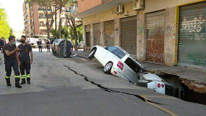 Dos coches atrapados en un enorme socavón en el barrio romano de Torpignattara, el pasado martes.