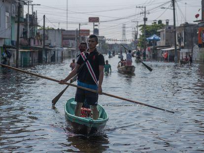 Los residentes locales usan botes en una calle inundada después de las fuertes lluvias en Villahermosa, Tabasco.
