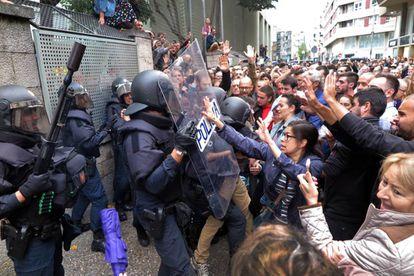 Votantes de un colegio electoral de Girona forcejean con agentes antidisturbios de la Policía Nacional que acudieron a clausurar el centro e incautarse de las urnas.