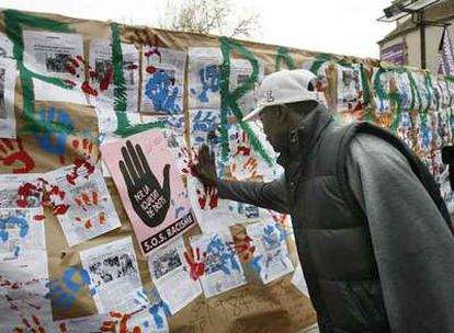 Un inmigrante participa en un acto antirracista en Barcelona en el que los ciudadanos pusieron su mano en un muro alzado simbólicamente contra la xenofobia.