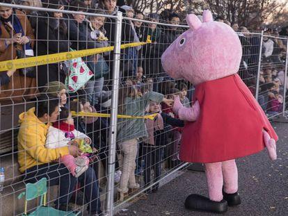 Una persona disfrazada de Peppa Pig saluda a los niños en el público durante la cabalgata de los Reyes Magos de este domingo en Madrid.