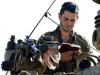 Un soldado israelí reza a bordo de un carro de combate cerca de la frontera entre Israel y Gaza.