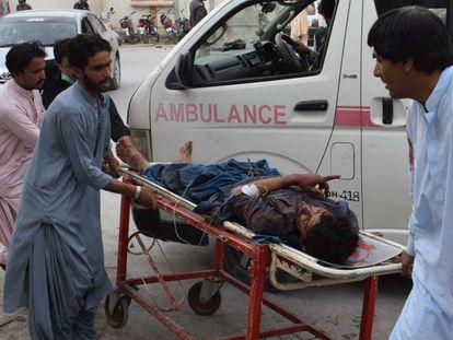 Una víctima del ataque suicida hoy en Pakistán en un mitin es evacuado de la zona de la explosión.