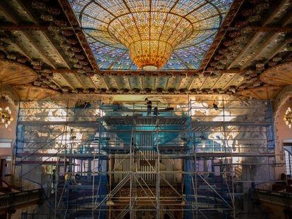 Un operario trabaja en el Palau de la Música durante la restauración del conjunto escultórico del escenario.
