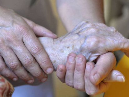 Una persona atiende a una anciana.