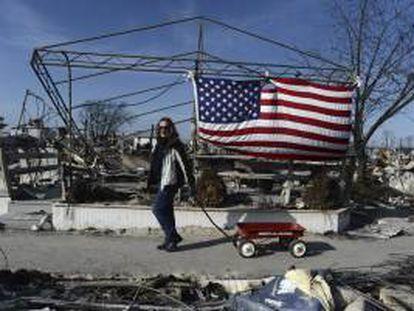 Una mujer pasa delante de una casa destruida por el paso del Huracán Sandy en Breezy Point, Nueva York, EE.UU..