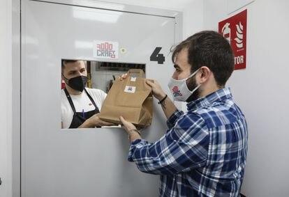 Juan Beltrán le entrega un pedido de FoodCraft a su socio, Juan Diego Gaitán, que se lo llevará a un repartidor que espera en la puerta del local en Tetuán donde está su cocina.