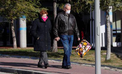 Una pareja con mascarillas, en el exterior del hospital de Torrejón de Ardoz.