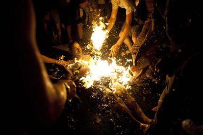Varias personas intentan apagar las llamas del manifestante que se prendió fuego.