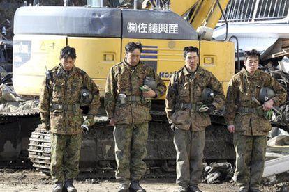 Soldados japoneses aguardan el momento de silencio en honor a las víctimas del terremoto y tsunami, en la ciudad de Miyako.