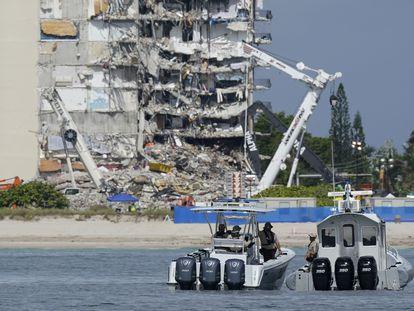 Botes de la policía de Miami vigilan a lo lejos los restos del edificio colapsado.