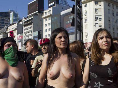 Tres mujeres muestran sus tetas rodeadas de hombres curiosos.