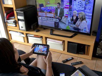 Una mujer ve la televisión en su casa.