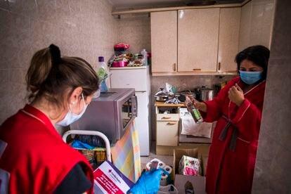 Sofía, voluntaria de Cruz Roja (izquierda), reparte alimentos en el piso en el que vive Mari Cruz (derecha), en San Sebastián de los Reyes (Madrid).
