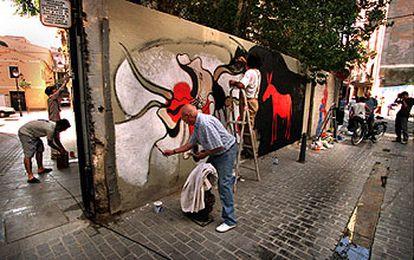 Participantes en la iniciativa <i>Pintamos algo?</i>, ayer, aplicándose a cambiar el rostro de los muros del barrio de El Carme de  Valencia.