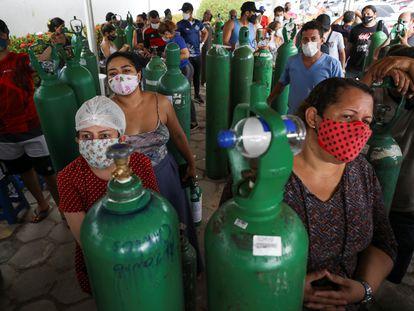 Familiares de enfermos con problemas respiratorios hacen cola para rellenar sus tanques con oxígeno en Manaos. En vídeo, un paciente de covid-19 es tratado en casa debido a la saturación hospitalaria en la capital de Amazonas.