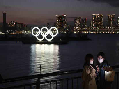 Dos jóvenes se hacen un selfie ante los anillos olímpicos en Tokio.