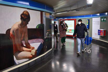Usuarios del Metro de Madrid, en el pasillo de una estación el pasado lunes.