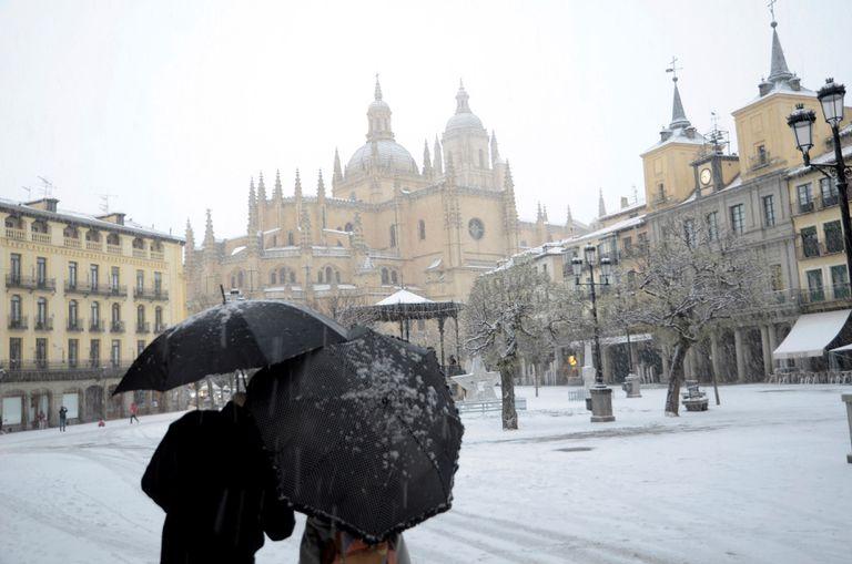 GRAF7184. SEGOVIA, 08/01/2021.- Dos personas caminan por la Plaza Mayor de Segovia durante una intensa nevada, este viernes, jornada marcada por el paso de la borrasca Filomena. EFE/ Pablo Martín