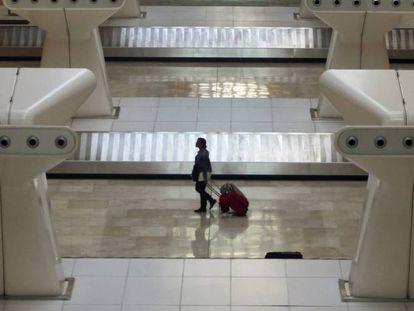 Una viajera en el área de recogida de equipajes del aeropuerto de Madrid-Barajas.
