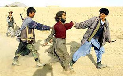 Dos combatientes de la Alianza del Norte custodian a un paquistaní que luchaba con los talibanes, capturado durante un ataque en la aldea de Quruq.