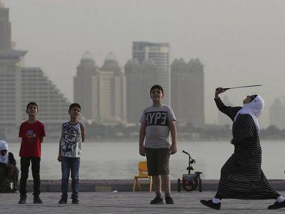 Una mujer juega con unos niños con una raqueta de bádminton el pasado mayo en Doha.