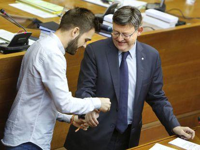 El diputado Fran Ferri coloca una pulsera reivindicativa LGTB al presidente Ximo Puig.