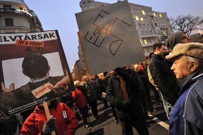 Un manifestante antigubernamental sostiene una pancarta con la esvástica hecha con las letras de Fidesz en Budapest.