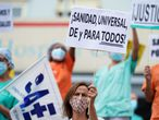 """A health worker holding a placard reading """"Universal healthcare for all"""" attends a protest against the regional health authority's lack of support and demanding better working conditions outside Gregorio Maranon hospital in Madrid, Spain September 15, 2020. REUTERS/Juan Medina"""