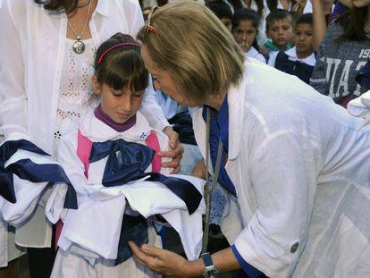 La ministra de Educación de Uruguay entrega materiales escolares a una niña durante la celebración del inicio del año escolar, en Montevideo.