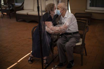 Agustina Cañamero, de 81 años, abraza y besa a su marido, Pascual Pérez, de 84, a través de una pantalla de plástico como medida preventiva contra el coronavirus en una residencia de ancianos en Barcelona, el 22 de junio de 2020.