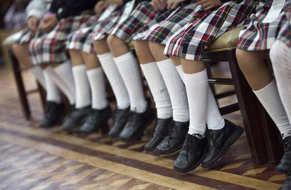 Un grupo de niñas de uniforme con falda.