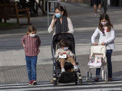 Una madre con tres niños pasea por San Sebastián.