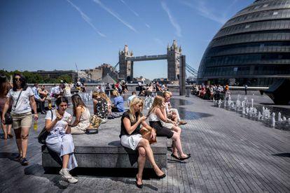 Turistas y ciudadano sen general se toman un descanso cerca de City Hall en el centro de Londres el 2 de julio de 2018