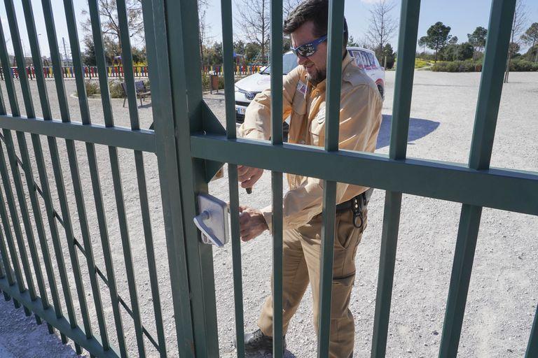 Un guardia de seguridad cierra una de las puertas del parque de Valdebebas este sábado