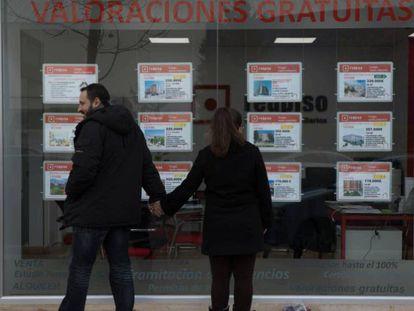 Dos jóvenes miran un escaparate con anuncios de pisos en el Ensanche de Vallecas (Madrid).